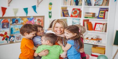 preschool teacher hugging children