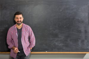 male teacher standing in front of chalkboard