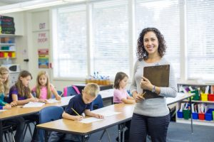 new teacher standing with book in front of her classroom