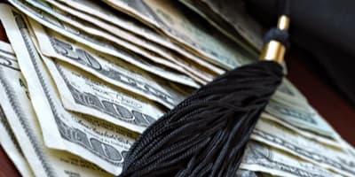 graduation tassel placed over dollar bills