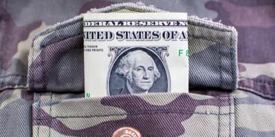 Dollar bill sticking out of camo pocket