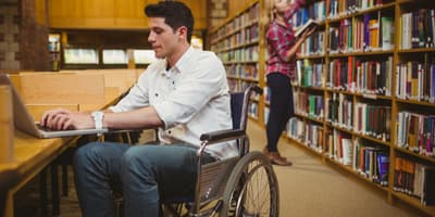 Student in wheelchair studying on computer at library