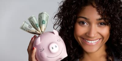 African American woman holding a piggy bank with money sticking out of it