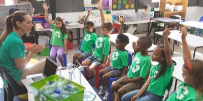 Kids wearing recycling shirts in a classroom