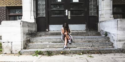student sitting on stairs outside of school with her head in her hands